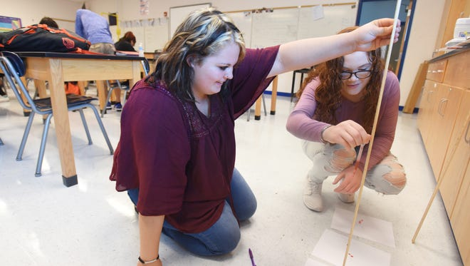 Miranda Rieder, left, and Courtney Royston measure (fake) blood splatter during Zanesville High School's biomedical class on Thursday. Classmembers have been examining a simulated crime scene since the first day of school.