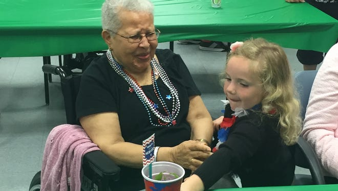 Petway Elementary School kindergartner Quinn Cleary gives a potted plant to N.J. Veterans Memorial Home resident Ernestine Harvey during her visit Thursday.