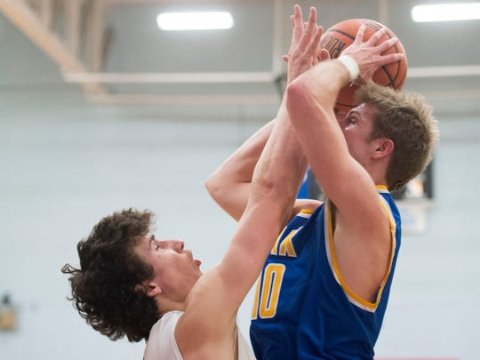 Christian Academy's Hunter Reynolds attempts to score while defended by Catholic's Brock Jancek in the Region 2-AA Boys Basketball Championship on Thursday, March 2, 2017, at Austin-East High School.