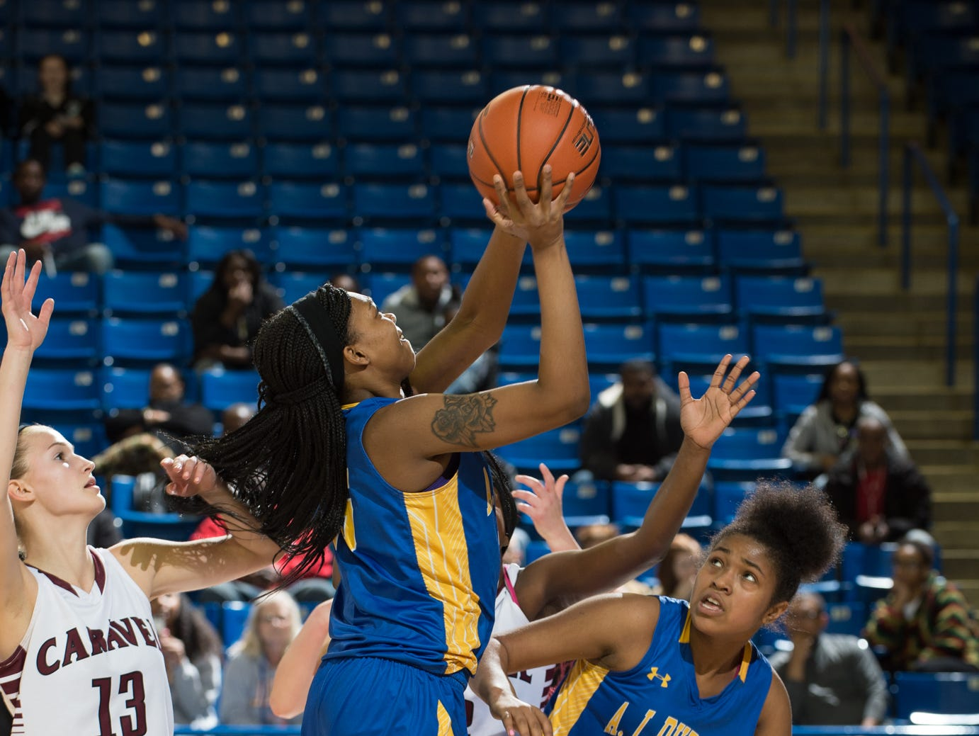 A.I. duPont's Al'kirah Wilson (15) goes for a shot in the quarterfinals of DIAA Girls Basketball Tournament at the University of Delaware against Caravel.