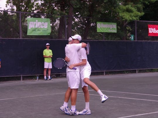 Peter (left) and son Tanner Smith of Los Angeles embrace after championship point.