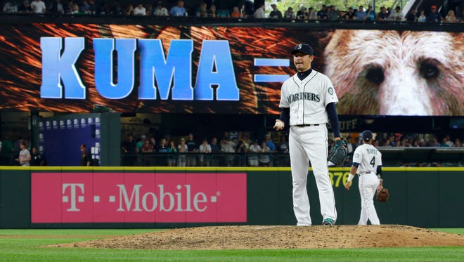 "Seattle Mariners starting pitcher Hisashi Iwakuma stands on the mound in the eighth inning of his no-hitter against the Baltimore Orioles, in front of an electronic sign that reads ""Kuma ="" and shows a photo of a bear, during a baseball game Wednesday, Aug. 12, 2015, in Seattle. The Japanese word ""kuma"" means ""bear"" in English. The Mariners won 3-0."