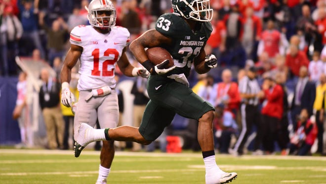 Michigan State Spartans running back Jeremy Langford (33) rushes into the end zone for a touchdown during the fourth quarter of the 2013 Big 10 Championship game against the Ohio State Buckeyes at Lucas Oil Stadium.