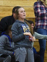 Reed's Emma Johnson watches a Reed boys basketball game from the stands last season.