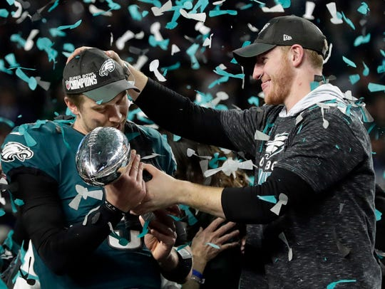 Eagles quarterback Carson Wentz, right, hands the Vince