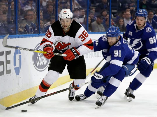 New Jersey Devils' Nick Lappin (36) and Tampa Bay Lightning center Steven Stamkos (91) chase a loose puck during the first period of an NHL hockey game Saturday, Feb. 17, 2018, in Tampa, Fla. Trailing the play is Lightning's defenseman Mikhail Sergachev (98). (AP Photo/Chris O'Meara)