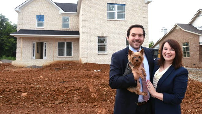 Cory and  Mallory Ricci pose for a photo with their dog Elle at their new home in Spring Hill, which is still under construction. They expect to close in October.