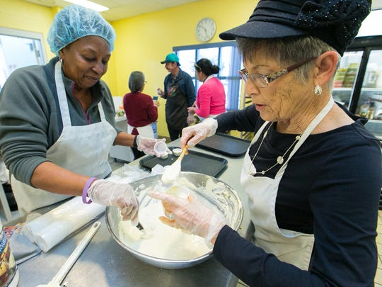 El Caldito Soup Kitchen volunteers Velma Noland, left and Mardelle Manes work together making and portioning out a secret pretzel-dip recipe on Wednesday in the kitchen.