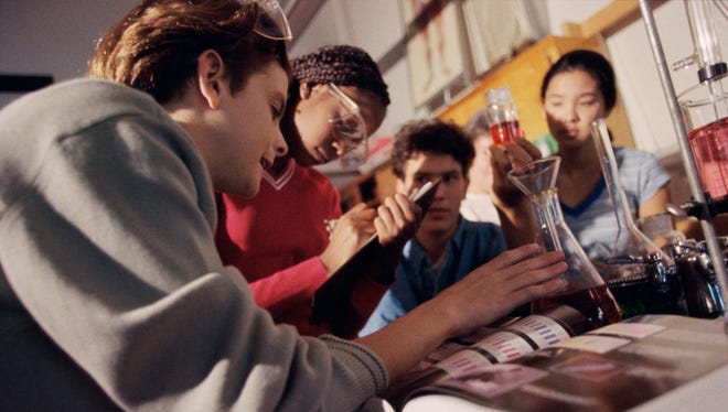 Teenagers conducting an experiment in a chemistry laboratory.
