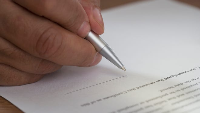 Stock image of a man signing a document