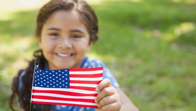 Stock image of a girl holding an American flag.