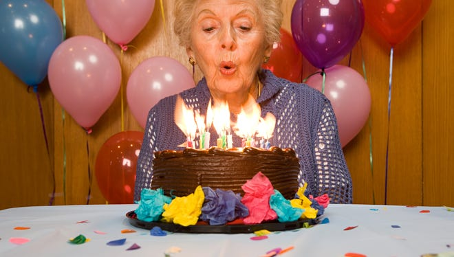 A woman blows out birthday candles on a cake.