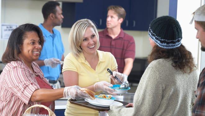 People volunteering at soup kitchen.