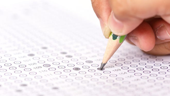 A student fills in a bubble answer sheet during a standardized test.