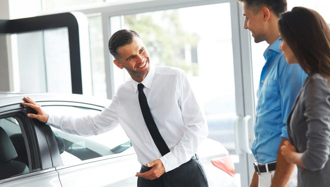 A sales staff member speaks to potential customers about buying a car.
