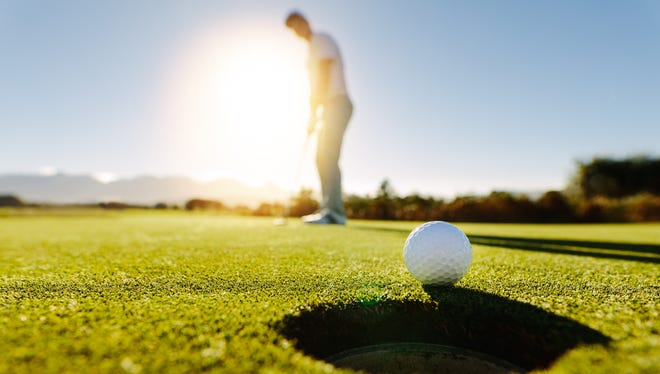 Pro golfer putting golf ball in to the hole. Golf ball by the hole with player in background on a sunny day.