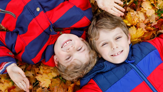 Two boys lying in autumn leaves