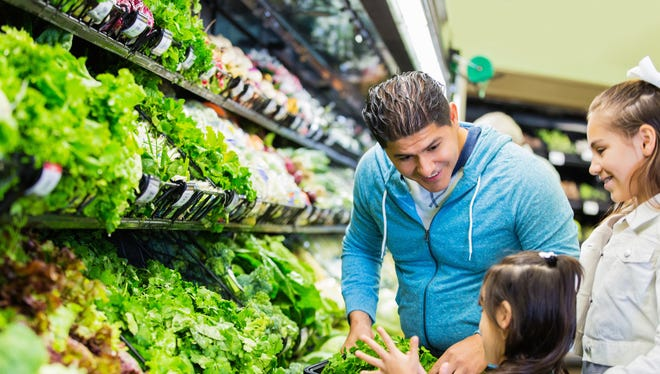 Mid adult Hispanic man is shopping in local grocery store or supermarket with two young daughters. Elementary age Hispanic little girls are helping father shop for healthy food in produce section. Children are selecting fresh vegetables. Man is holding shopping basket.