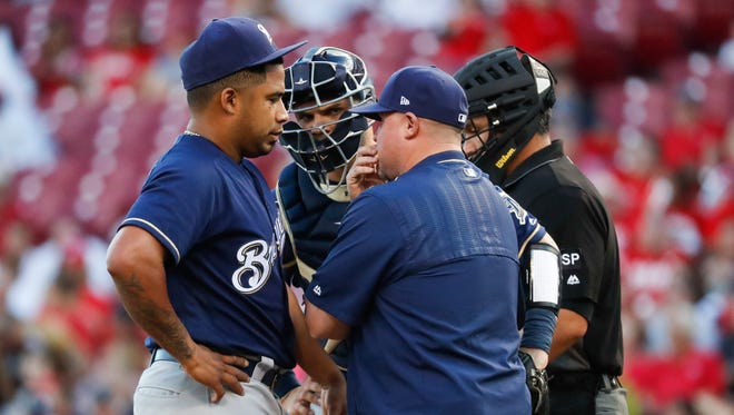 Brewers pitcher Junior Guerra (left) meets with catcher Manny Pina and pitching coach Derek Johnson during a game.