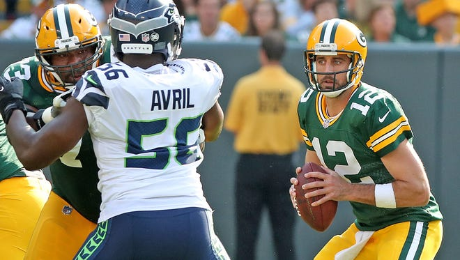 Green Bay Packers quarterback Aaron Rodgers (12) looks for a receiver as offensive guard Jahri Evans (73) blocks out defensive end Cliff Avril (56) against the Seattle Seahawks Sunday, September 10, 2017 at Lambeau Field in Green Bay, Wis.