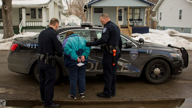 Port Huron Police officers Don Ochadleus and Bryan Coleman arrest a woman for a personal protection order violation Tuesday in the 1200 block of Varney in Port Huron. While overall crime in the city of Port Huron has decreased, robberies increased by 35.5 percent from 2013 to 2014.