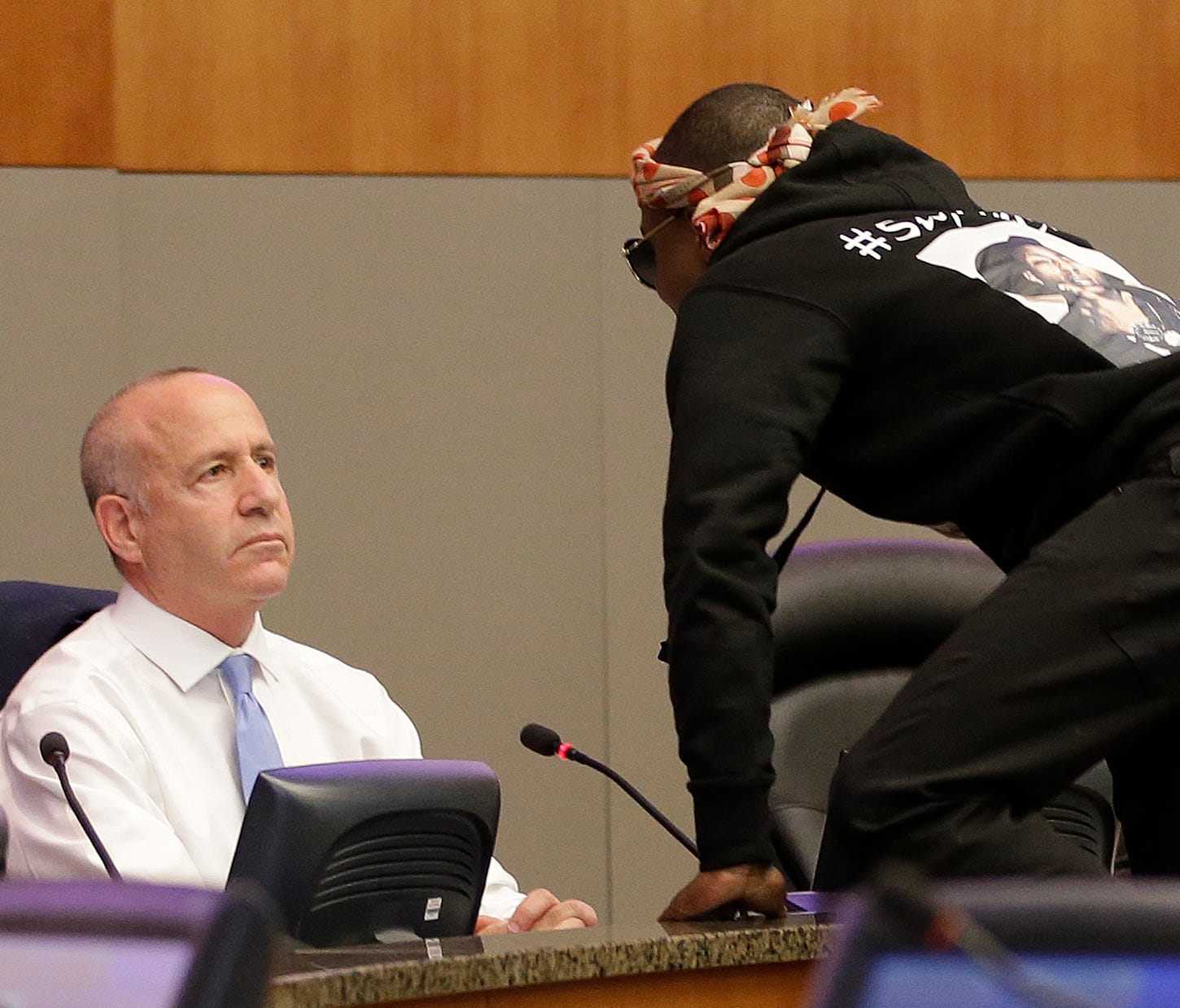 Stevante Clark jumps on the dais and shouts at Sacramento Mayor Darrell Steinberg, left, during a city council meeting, Tuesday, March 27, 2018, in Sacramento, Calif.