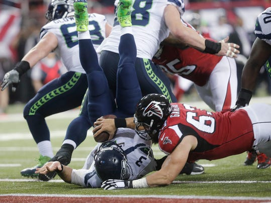 FILE - In this Jan. 14, 2017, file photo, Atlanta Falcons' Ben Garland (63) falls onto Seattle Seahawks quarterback Russell Wilson (3) for a Falcons safety during an NFL football divisional playoff game in Atlanta. Garland could be one of the rare players to go both ways in the Super Bowl, a valuable backup on Atlanta's offensive and defensive lines in addition to his special teams duties. (AP Photo/John Bazemore, File)