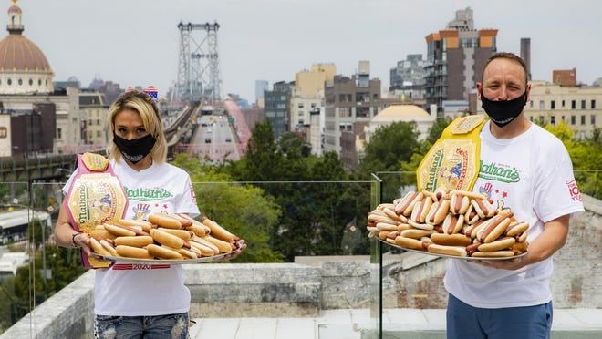 Competitive eaters Miki Sudo, left, and Joey Chestnut, right, pose for a photograph after a weigh-in before the Nathan's Famous July Fourth hot dog eating contest, Friday, July 3, 2020, in the Brooklyn borough of New York. The weigh-in was held in a private, socially-distanced ceremony in the Williamsburg neighborhood due to COVID-19 concerns.