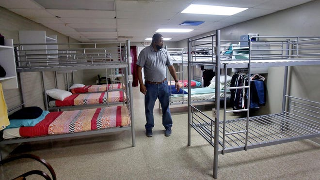 Executive director of Western Carolina Rescue Ministries Micheal Woods walks through one of two renovated bunk rooms at Abba's Love in Shelby.