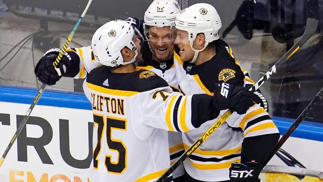 The Bruins' Connor Clifton and Charlie Coyle, right, celebrate with Sean Kuraly, center, who scored a third-period goal against the Hurricanes in Game 3 of their Stanley Cup playoff series on Saturday.
