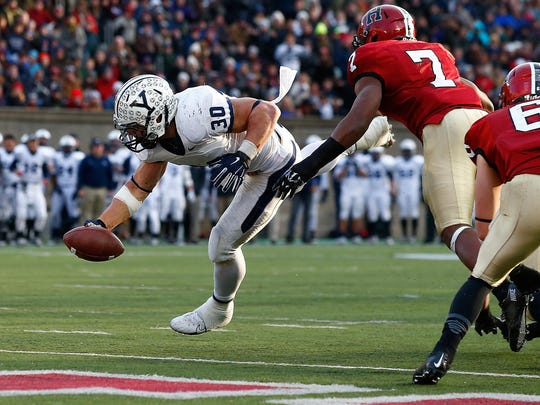 Tyler Varga #30 of the Yale Bulldogs reaches for a touchdown past Norman Hayes #7 of the Harvard Crimson during their 131st meeting on November 22, 2014 in Boston, Massachusetts.