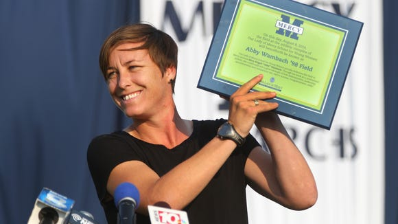 Abby Wambach displays a plaque she received as the playing field at Mercy high school was named in her honor.
