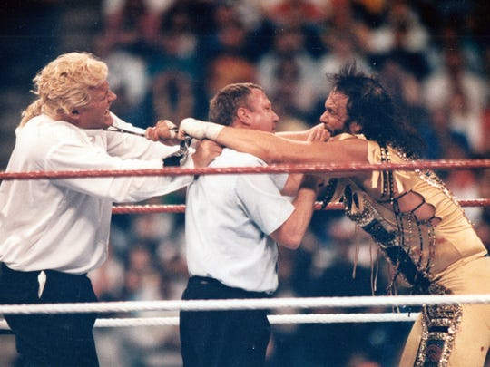 "Randy ""Macho Man"" Savage, right, reaches over a referee to engage with Mr. Perfect during WrestleMania VIII, which was held in April 1992 at the Hoosier Dome."