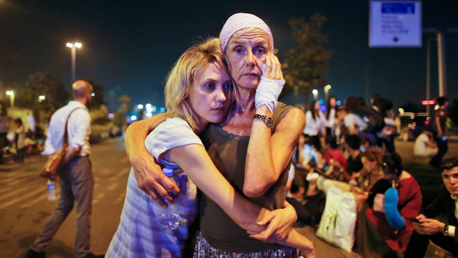 Passengers embrace each other as they wait outside Istanbul's Ataturk airport on June 29, 2016, following their evacuation after a blast.