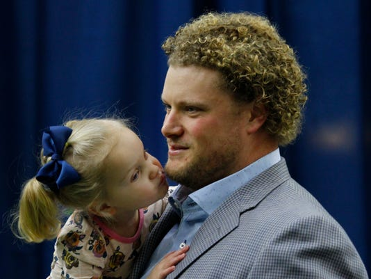 Buffalo Bills center Eric Wood is kissed by daughter Grace following a press conference announcing he has been diagnosed with a career ending neck injury, Monday, Jan. 29, 2018, in Orchard Park, N.Y. (AP Photo/Jeffrey T. Barnes)