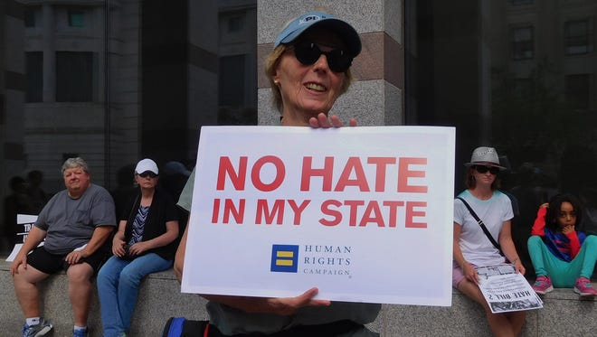 A protester holds a sign during a protest of HB2 last year in Raleigh in this file photo.