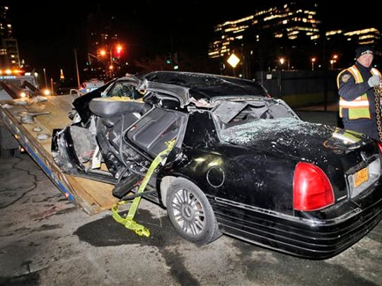 """A police officer tows a car following an accident in New York, Wednesday, Feb. 11, 2015, that killed longtime """"60 Minutes"""" correspondent Bob Simon. Simon covered riots, Academy Award-nominated movies and wars and was held captive for more than a month in Iraq two decades ago. He was 73. (AP Photo/Kathy Willens)"""
