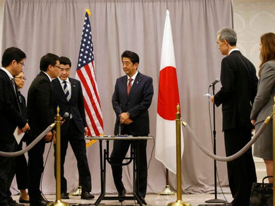 Japanese Prime Minister Shinzo Abe, center, listens to questions from members of the press after meeting with President-elect Donald Trump, Thursday, Nov. 17, 2016, in New York. Abe made a stop in New York to meet with the president-elect while en route to an APEC meeting in Lima.