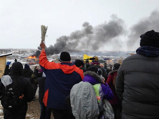 A fire burns in the background as opponents of the Dakota Access pipeline leave their main protest camp Wednesday, Feb. 22, 2017, near Cannon Ball, N.D., as authorities were preparing to shut down the camp in advance of spring flooding season. The Army Corps of Engineers ordered the camp closed at 2 p.m. Wednesday.