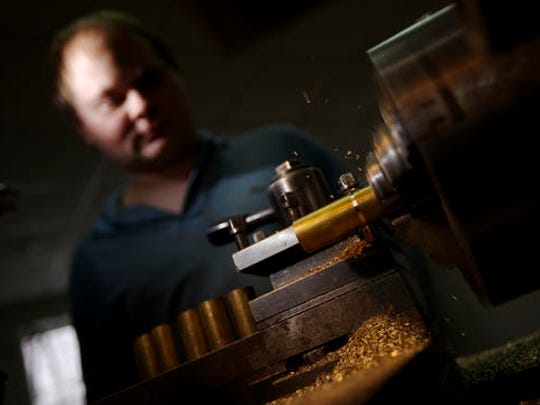 On this Thursday, Feb. 9, 2017 photo operator Roman Ilyukhin lathes a brass bar to make a microphone's part at a factory in Tula, Russia. In Tula, a city packed with the Russian defence industry, Californian musician David Brown and fan Pavel Bazdyrev have been making high-end microphones since 2014, taking advantage of cheap labor and second hand machinery from Kalashnikov arms plants. Ilyukhin, says his wage of 60,000 rubles ($1,000) is almost double what he used to earn elsewhere in the city.