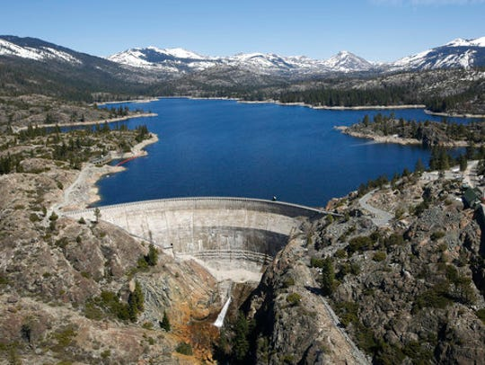 In this April 3, 2017 photo, snow covering the Sierra Nevada is seen in the background of the PG&E hydroelectric dam at Spaulding Lake in Nevada County, California.