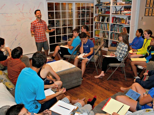 Students listen to Burlington parent Jeff Wick explain a concept during a math lesson in the living room of Wick's home on Oct. 5.