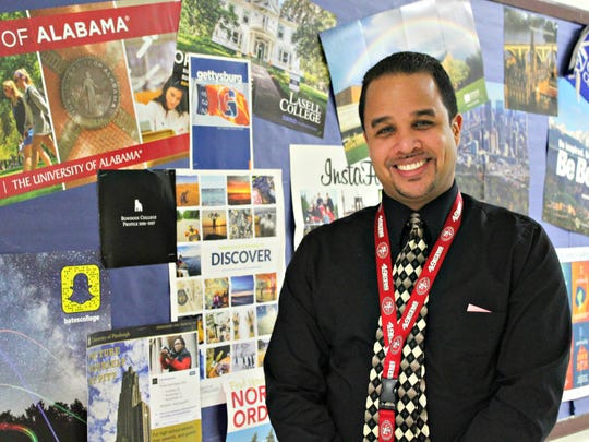Mario Macias, the guidance director at Burlington High School, stands in front of college posters at the school on Wednesday, Dec. 14, 2016. The counselor has heard a lot of concerns from parents, teachers and community members about the new system.