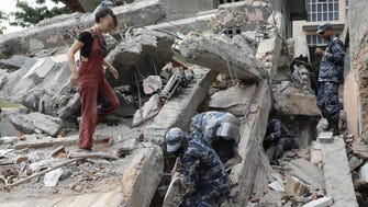 An unidentified tourist, left, stands as members of a rescue team search for victims under the rubble of a hotel in Thamel, a tourist hub in Kathmandu on April 26, 2015.