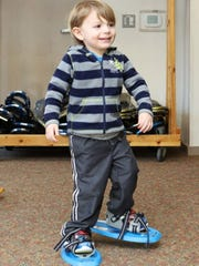 Griffin Weber, 2, of Waukesha, tests toddler snowshoes