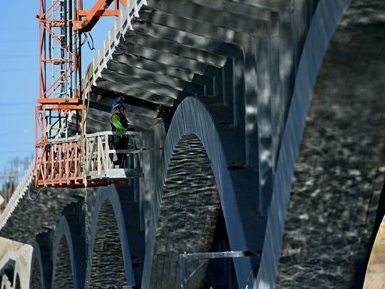 A construction crew repairs joints in the 10th Street Bridge deck in 2015 by adding new concrete. Tribune file photo/Rion Sanders