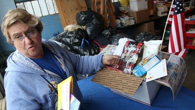 Ronnie Micciulla, founder and executive director of the American Recreational Military Services in Toms River, shows the contents of one of the boxes that will be shipped to a serviceman overseas.