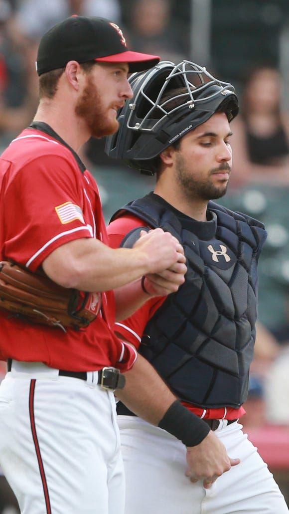 El Paso catcher Austin Hedges and pitcher Michael Kelly talk on the mound during a break Thursday.