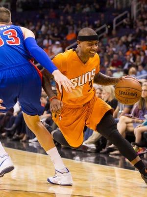 Suns' Isaiah Thomas comes around the defense of Pistons' Jonas Jerebko at US Airways Center in Phoenix on Dec. 12, 2014.