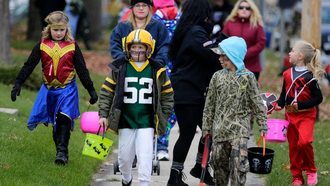 Sidewalks are crowded with families as trick-or-treat takes place Sunday, October 29, 2017, in Hortonville, Wis.